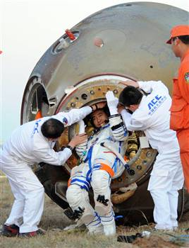 A taikonaut emerges from China's Shenzhou 7 spacecraft after a successful orbital flight