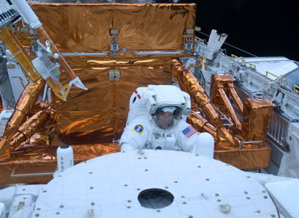 Astronaut Mike Massimino works with the Hubble Space Telescope in the cargo bay of the Earth-orbiting space shuttle Atlantis. Photo Credit: NASA