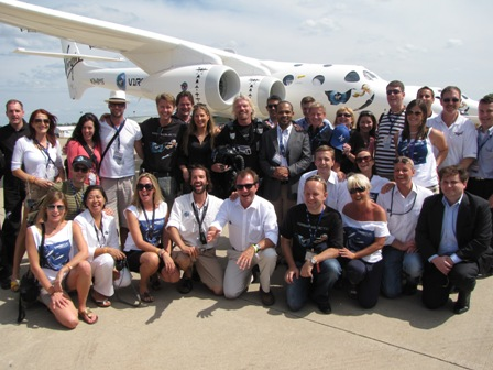 Richard Branson poses with Virgin Galactic ticketholders and staff members in front of WhiteKnightTwo.