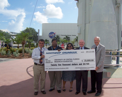Participating in the check presentation at the Kennedy Space Center Visitor Complex Rocket Garden are, from left, Robert Crabbs, associate director of UCF's Florida Space Institute; Jaydeep Mukherjee, director, NASA Florida Space Grant Consortium, and interim director, Florida Space Institute; Sreela Mallick, assistant director, NASA Florida Space Grant Consortium; Roy D. Bridges, Jr., director, Space and Science Services, Northrop Grumman Technical Services, and Roy Tharpe, director, Space and Science Services, Northrop Grumman Technical Services and chairman of the National Space Club Florida Committee.