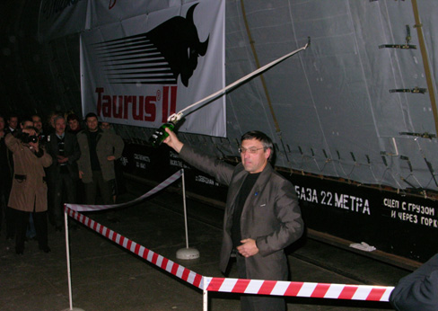 A Yuzhnoye official prepares to smash a champagne bottle against the side of the first Taurus II first stage. (Credit: Yuzhnoye