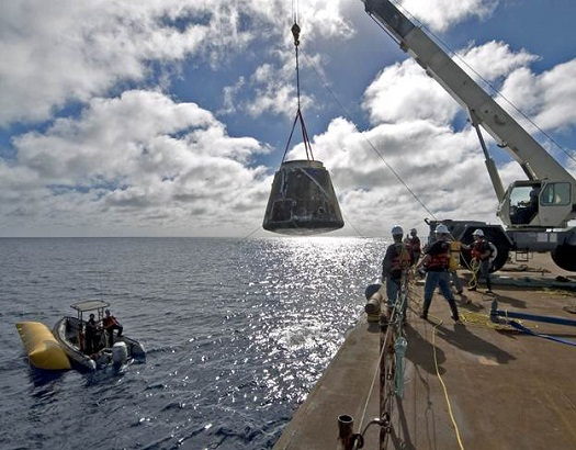A crane lifts SpaceX's Dragon spacecraft on to a barge after the vehicle twice orbited the Earth in December of 2010.  (Credit: SpaceX)