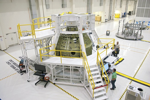 Inside the Operations and Checkout Building, a birdcage tool along with work platforms surround the Orion Exploration Flight Test 1 crew module. (Credit: NASA/Charisse Nahser)