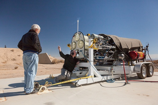 XCOR CEO Jeff Greason inspects the Lynx main engine after a hotfire test while Chief Test Engineer Doug Jones looks on. (Credit: XCOR)