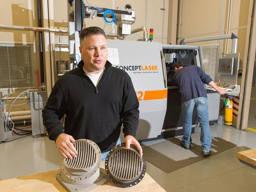 Andy Hardin, SLS subsystem manager for liquid engines, compares the process of creating a rocket engine part using traditional manufacturing and welding, at right, and making one using Selective Laser Melting, or SLM, at left. The new z-baffle for the RS-25 engine was created by fusing metal dust with a high-power laser using the machine in the background. (Credit: NASA/MSFC)