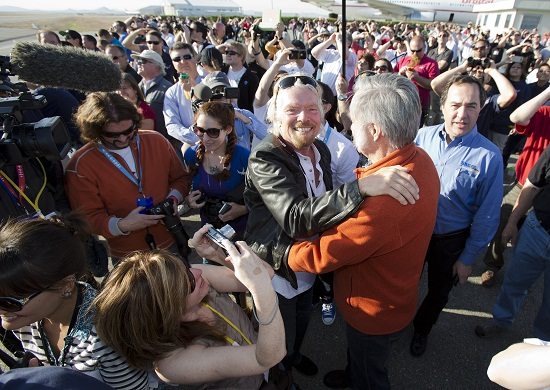 "Sir Richard Branson hugs designer Burt Rutan as they are surrounded by employee's of Virgin Galactic, The SpaceShip Company and Scaled Composites watch as Virgin Galactic's SpaceShip2 streaks across the sky under rocket power, its first ever since the program began in 2005. Burt's wife Tonya Rutan is at right taking their photo. The spacecraft was dropped from its ""mothership"", WhiteKnightTwo over the Mojave, CA area, April 29, 2013 at high altitude before firing its hybrid power motor. (Credit: Mark Greenberg)"