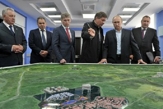 Russian President Vladimir Putin looks over plans for Vostochny. (Credit: Roscosmos)