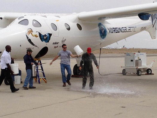 "New Virgin Galactic pilot Frederick ""CJ"" Sturckow get the traditional post-flight drenching after flying WhiteKnightTwo for the first time. (Credit: Virgin Galactic)"