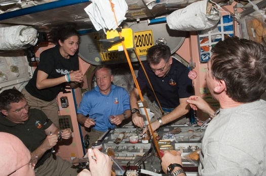Expedition 26 and STS-133 crew members share a meal in the Unity node of the International Space Station. (Credit: NASA)