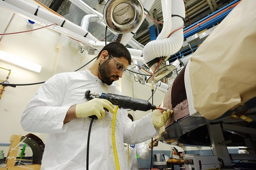"Textron technicians apply the Avcoat material by ""gunning"" the material into each of the 330,000 individual cells of the honeycomb structure. (Credit: NASA)"