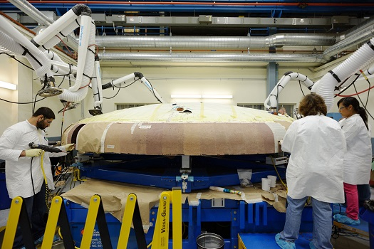 A team of technicians at Textron Defense Systems apply Avcoat ablative material to the composite honeycomb structure attached to the Orion heat shield carrier structure. The ablative material is designed to protect the spacecraft from extreme temperatures during re-entry. (Credit:  NASA)