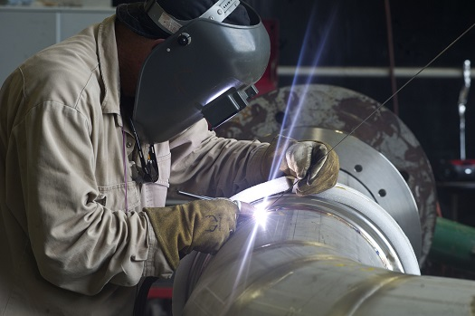 A welder at NASA's Stennis Space Center works on a portion of piping to be installed on the A-1 Test Stand for RS-25 rocket engine testing. (Credit: NASA/SSC)