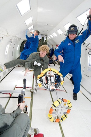 CU-Boulder students test the behavior of DANDE satellite parts in a modified NASA jet that creates microgravity conditions. Former CU-Boulder student Matt Capron, in green jumpsuit, is shown here. (Credit: CU-Boulder)
