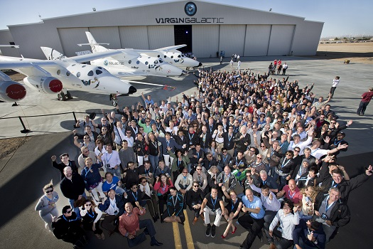 A majority of Virgin Galactic's future Astronauts gather with Sir Richard Branson (center) for a group photo at Virgin Galactic FAITH hangar in Mojave, CA September 25, 2013. AT side is the WhiteKnight2 mated with SpaceShip2. (Credit: Virgin Galactic)