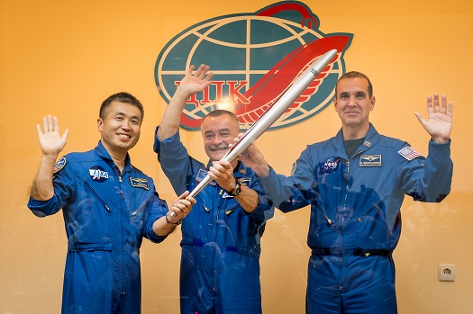 From left, Expedition 38 Flight Engineer Koichi Wakata of the Japan Aerospace Exploration Agency, Soyuz Commander Mikhail Tyurin of Roscosmos, and Flight Engineer Rick Mastracchio of NASA, smile and wave as they hold an Olympic torch that will be flown with them to the International Space Station. (Credit: NASA/Bill Ingals)