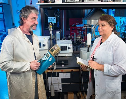 Paul Greenberg demonstrates the Microscale Particulate Classifier to Luz Jezirorowski, chief of occupational health at NASA's Glenn Research Center in Cleveland. The larger standard electric mobility classifier and detector are in the background. (Credit: NASA)
