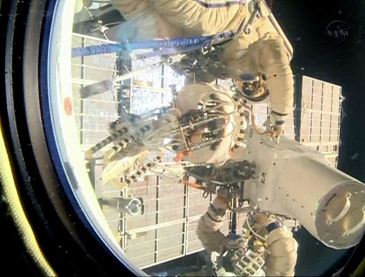 Spacewalkers Oleg Kotov and Sergey Ryazanskiy remove the high resolution camera they installed earlier during Friday's spacewalk. (Credit: NASA)