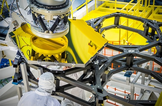 The robotic arm lifts and lowers a golden James Webb Space Telescope flight spare primary mirror segment onto a test piece of backplane at NASA's Goddard Space Flight Center in Greenbelt, Md. (Credit: NASA/Chris Gunn)