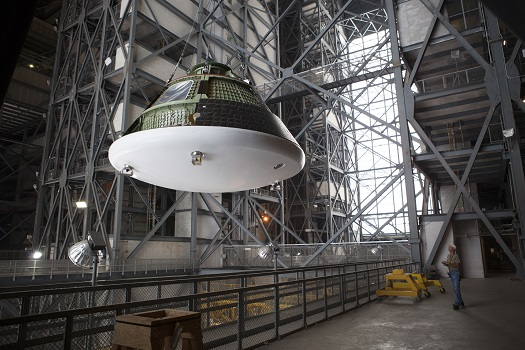 At NASA's Kennedy Space Center in Florida, the Orion ground test vehicle has been lifted high in the air by crane in the transfer aisle of the Vehicle Assembly Building. (Credit: NASA/Dimitri Gerondidakis)