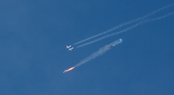 SpaceShipTwo lights its engine as WhiteKnightTwo flies overhead. (Credit: Ken Brown)