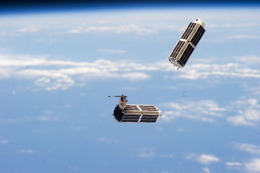 Two of the 28 Planet Labs Dove satellites that make up the Flock 1 constellation are seen launching into orbit from the International Space Station on Feb. 11. (Credit: NASA)