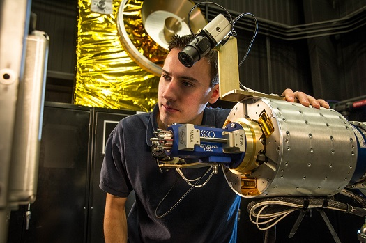 RROxiTT lead roboticist Alex Janas stands with the Oxidizer Nozzle Tool as he examines the work site. (Credit: NASA/Chris Gunn)