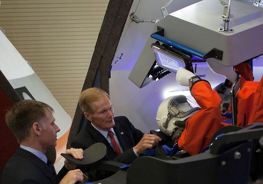 U.S. Sen. Bill Nelson, center, and former astronaut Chris Ferguson survey a mockup of the CST-100 spacecraft under development by The Boeing Company during a ceremony detailing Boeing's plans to use Orbiter Processing Facility-3 as a manufacturing hub for the capsule-shaped spacecraft. (Credit: NASA/Kim Shiflett)