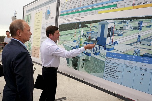Vladimir Putin reviews a map showing the plan for the Vostochny spaceport. (Credit: Presidential Press and Information Office)