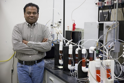Pratap Pullammanappallil poses in his lab next to an anaerobic digester, which turns human waste into rocket fuel. (Credit: University of Florida)