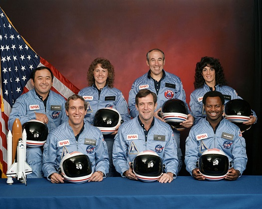 "Challenger crew. Back row, left to right: mission specialist Ellison Onizuka, payload specialist Christa McAuliffe, payload specialist Gregory Jarvis, mission specialist Judith Resnik. Front row left to right: pilot Michael J. Smith, commander Francis ""Dick"" Scobee, mission specialist Ronald McNair. (Credit: NASA)"