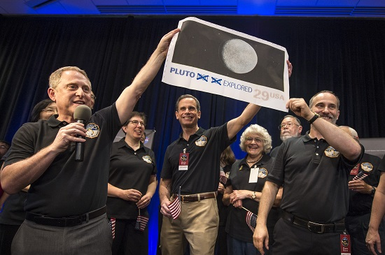New Horizons Principal Investigator Alan Stern of Southwest Research Institute (SwRI), Boulder, CO., left, Johns Hopkins University Applied Physics Laboratory (APL) Director Ralph Semmel, center, and New Horizons Co-Investigator Will Grundy Lowell Observatory hold a print of an U.S. stamp with their suggested update since the New Horizons spacecraft has explored Pluto, Tuesday, July 14, 2015 at the Johns Hopkins University Applied Physics Laboratory (APL) in Laurel, Maryland. (Credit: NASA/Bill Ingalls)