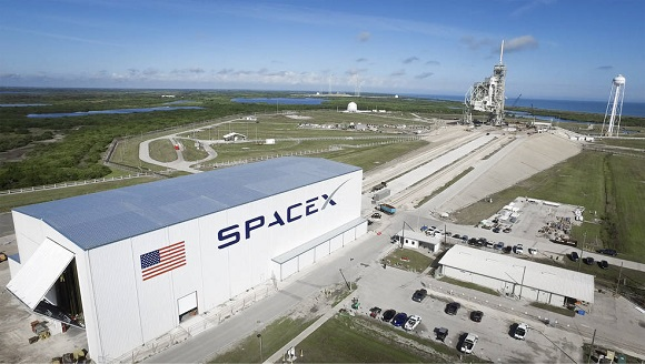 Launch Pad 39A at NASA's Kennedy Space Center in Florida undergoes modifications by SpaceX to adapt it to the needs of the company's Falcon 9 and Falcon Heavy rockets, which are slated to lift off from the historic pad in the near future. A horizontal integration facility has been constructed near the perimeter of the pad where rockets will be processed for launch prior of rolling out to the top of the pad structure for liftoff. SpaceX anticipates using the launch pad for its Crew Dragon spacecraft for missions to the International Space Station in partnership with NASA's Commercial Crew Program. (Credit: SpaceX)