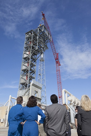 Commercial Crew astronauts Bob Behnken and Suni Williams, along with employees of United Launch Alliance and other companies, watch as a crane lifts a 15-foot-long, 650-pound beam to the top of the Crew Access Tower. (Credit: NASA/Kim Shiflett)