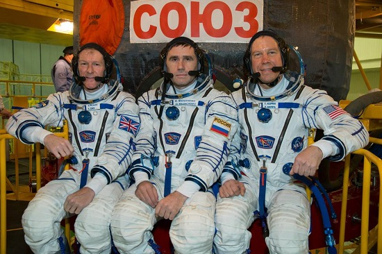 Expedition 46-47 crewmembers Tim Peake of the European Space Agency (left), Yuri Malenchenko of the Russian Federal Space Agency (Roscosmos, center) and Tim Kopra of NASA (right) pose for photos Dec. 1 in front of their Soyuz TMA-19M spacecraft during a crew fit check. (Credits: NASA/Victor Zelentsov)