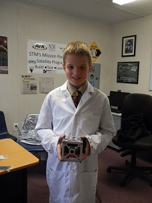 A student from St. Thomas More Cathedral School holds the STMSat-1 CubeSat. (Credit: St. Thomas More Cathedral School)