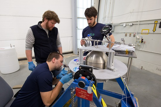 A Goddard team, led by engineer Henry Mulkey (middle), prepares a tank containing a Swedish-developed green propellant before its simulated loading at the Wallops Flight Facility late last year. Kyle Bentley (squatting) and Joe Miller (standing to the right of Mulkey) assisted in the demonstration. (Credits: NASA/C. Perry)