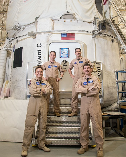 "Crew members for the current simulation missions stand in front of the NASA Human Exploration Research Analog (HERA). HERA 10 ""launched"" on May 2 for a 30-day mission to the near-Earth asteroid ""Geographos."" The crew members are (left to right): Chris Matty of Houston, Texas; Oscar Mathews of Virginia Beach, Virginia; Ron Franco of Lockport, New York; and Casey Stedman of Olympia, Washington. (Credit: NASA) Subject: Crew photo for HERA 10 crew. Photographer: Bill Stafford"