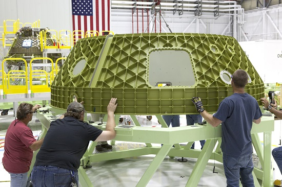 Technicians lower the upper dome of a Boeing Starliner spacecraft onto a work stand inside the company's Commercial Crew and Cargo Processing Facility at NASA's Kennedy Space Center in Florida. The upper dome is part of Spacecraft 1, a Starliner that will perform a pad abort flight test as part of the development process of the spacecraft in partnership with NASA's Commercial Crew Program.  (Credit: NASA/Dimitri Gerondidakis)