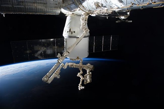 Dextre at the end of Canadarm2 preparing to remove cargo from Dragon. (Credit: NASA)