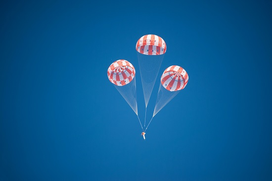 An Orion test article descends under three main parachutes during the first evaluation to qualify the spacecraft's parachute system for flights with astronauts. (Credit: NASA)