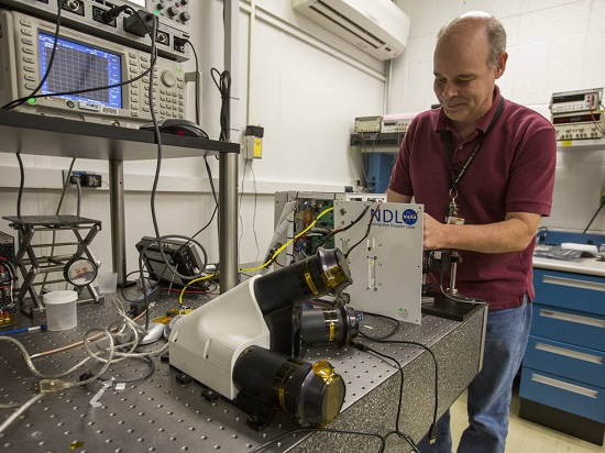 Bruce Barnes, who does electronics engineering and system integration for the Navigation Doppler Lidar, makes final preparations to the sensor in a lab at NASA's Langley Research Center. (Credit: NASA/David C. Bowman)