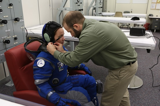 A suit technician fits the communications carrier on an astronaut stand-in before pressurizing the spacesuit inside Crew Quarters at NASA Kennedy Space Center in Florida. (Credit: NASA/Cory Huston)