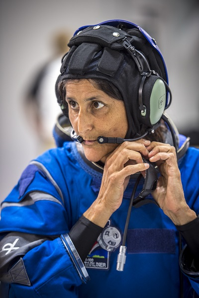 Astronaut Sunni Williams puts on the communications carrier of Boeing's new Starliner spacesuit. (Credits: Boeing)